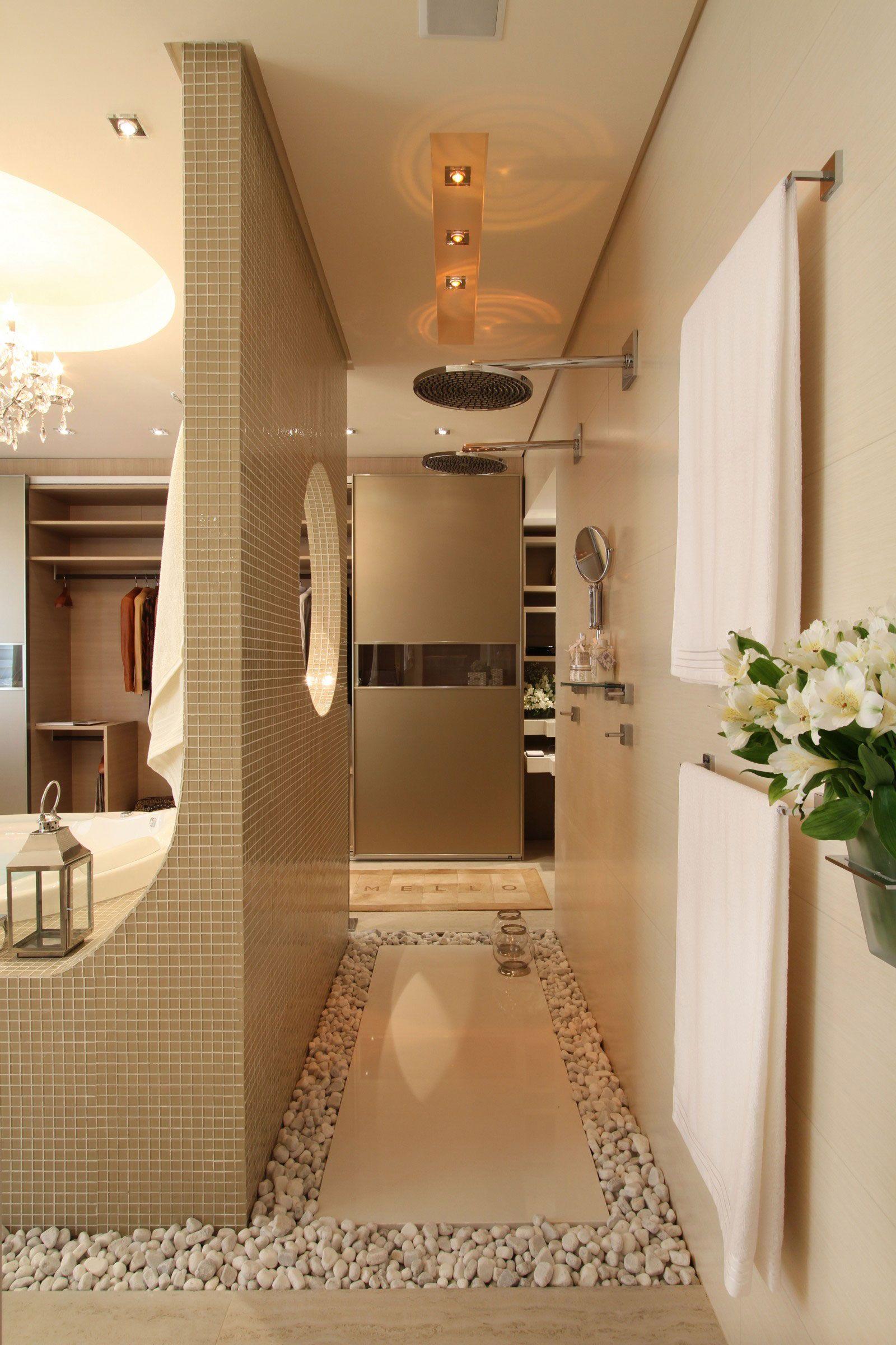 Os chuveiros ficam em uma localização privilegiada e são decorados por pedrinhas no piso.