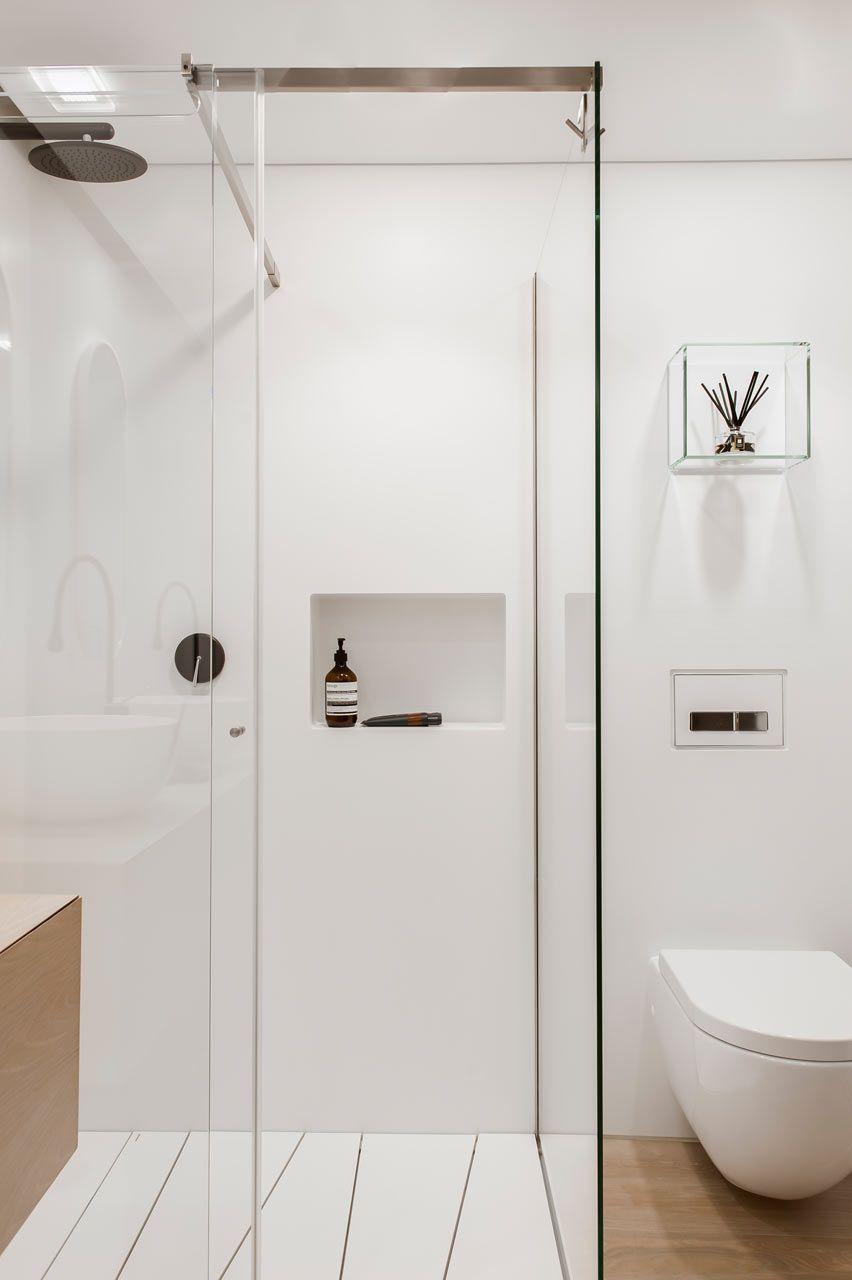Um banheiro clean com o uso de materiais leves e tons claros.