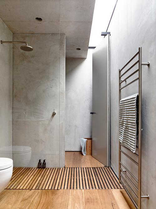 Banheiro moderno com cimento queimado e madeira.