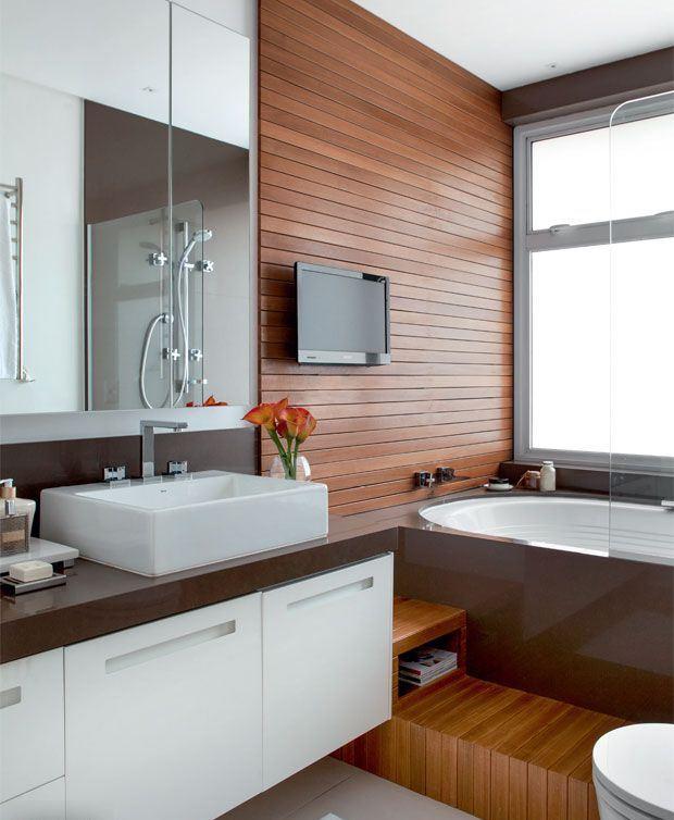 Esse banheiro conta com o espaço para um TV fixada no painel.