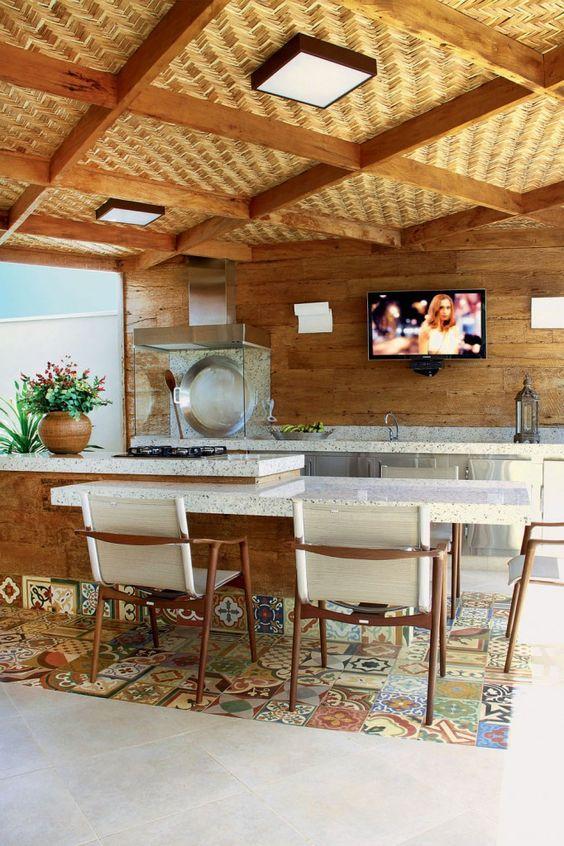 Tons de madeira, ladrilhos e churrasqueira em vidro criam um ambiente moderno e aconchegante
