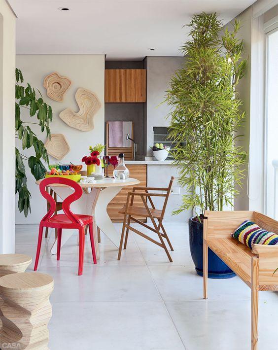 A churrasqueira em concreto deixa o ambiente neutro. Os acessórios coloridos podem complementar a decoração