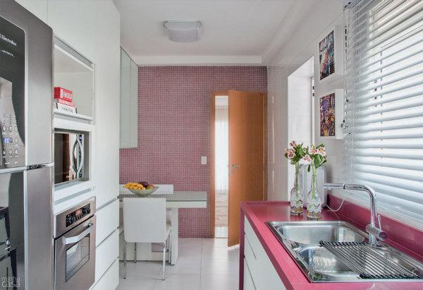 A bancada rosa compôs com o revestimento de fundo da cozinha