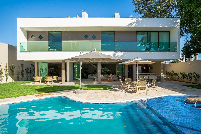 Modelo de casa com guarda-corpo de vidro e piscina nos fundos