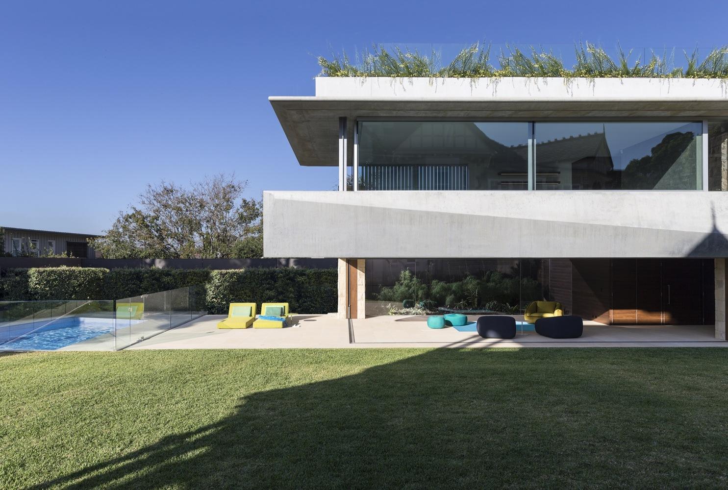 Área externa de casa luxuosa com piscina, área verde e guarda-corpo de vidro