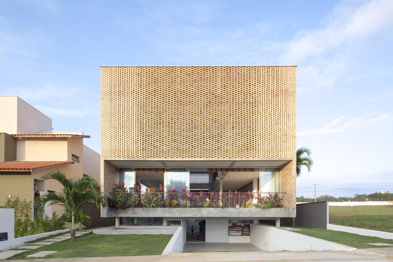 A composição dos tijolos permite uma abertura na fachada desta casa bonita