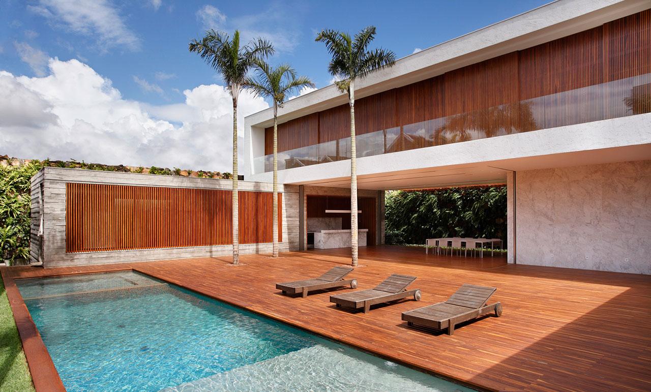 Fundos de uma casa bonita com deck de madeira e guarda-corpo de vidro na varanda do pavimento superior