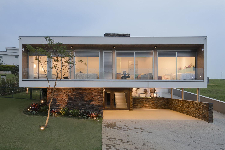 Neste projeto, o volume do pavimento superior é o destaque. No pavimento térreo, pedras complementam o revestimento do muro