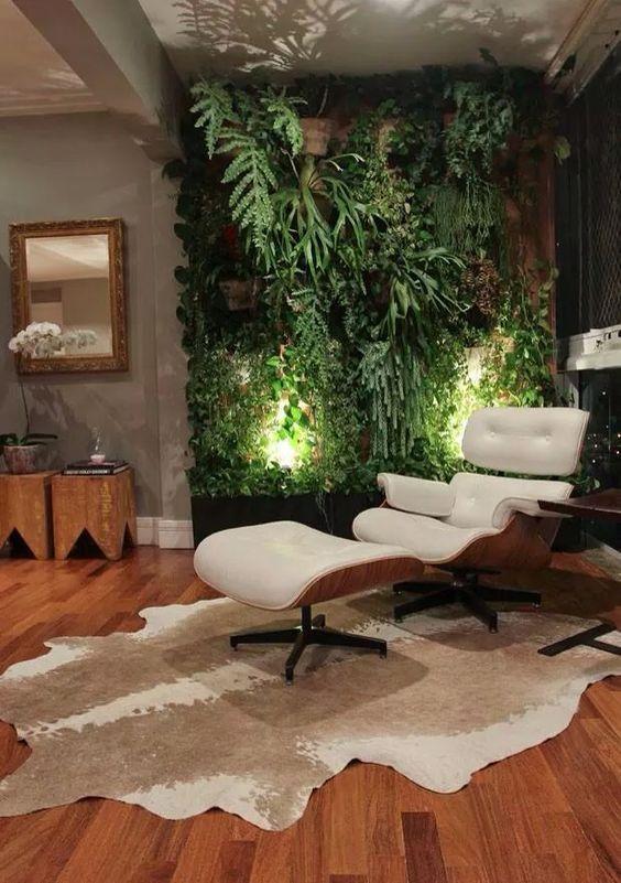 Com o fechamento da sacada, esse cantinho relaxante levou uma poltrona moderna e uma parede verde muito bem cuidada