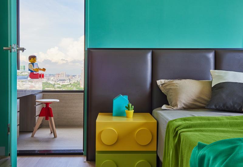 O quarto de lego levou uma cabeceira em tom de grafite para destacar o colorido da decoração