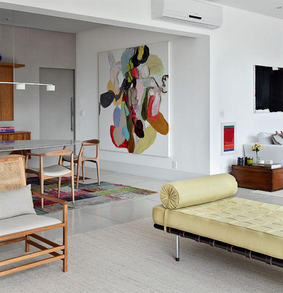 A chaise amarela combinou com o tapete e o quadro na parede desse ambiente integrado