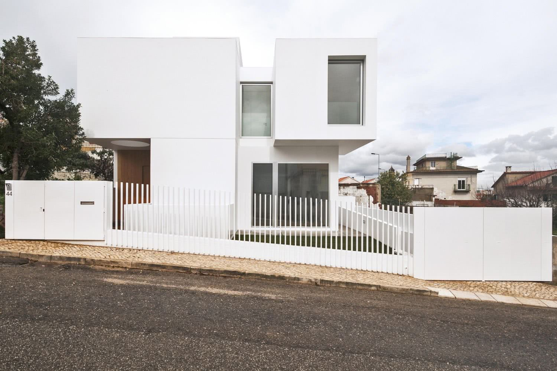 Portão vazado com gradil branco.