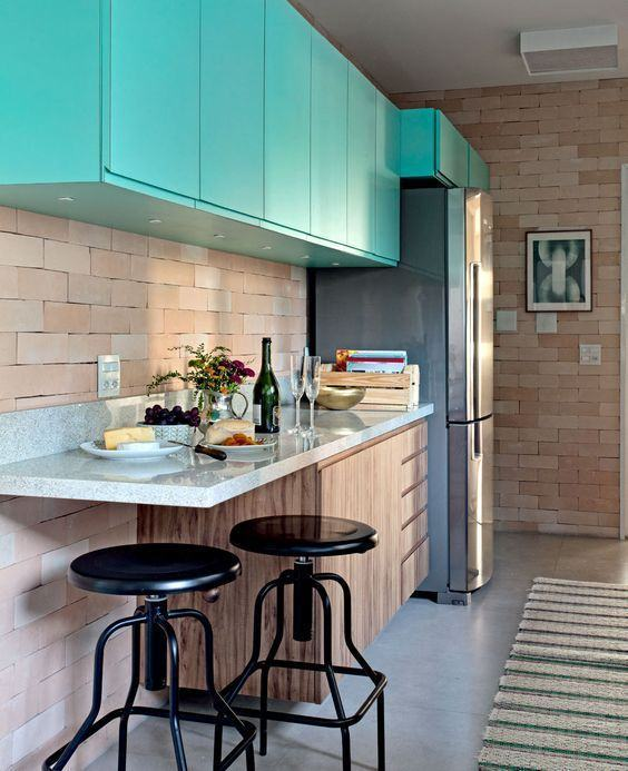 Composição perfeita de materiais: madeira na cor natural, tijolo a vista e armários azul