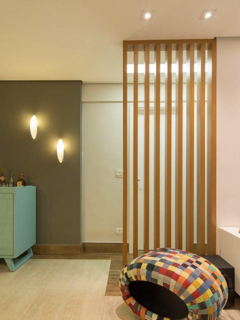 O painel ripado separa o hall de entrada da sala de estar de forma moderna e elegante!