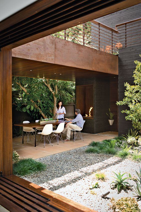 Jardim em espaço aberto da residência ao lado da mesa da churrasqueira
