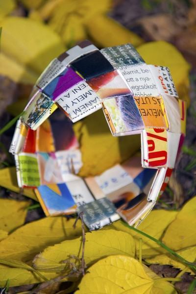 Pequeno bracelete feito com camadas de papel de revista e jornal