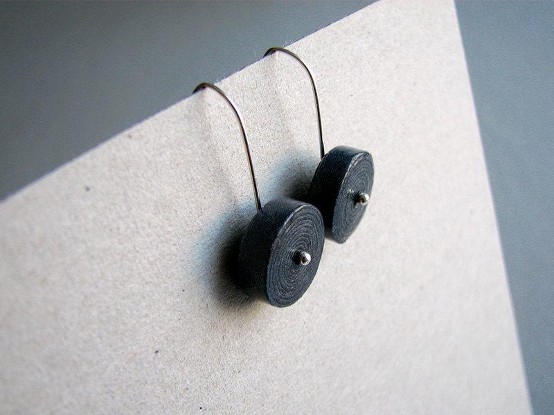 Pequeno brinco preto feito com jornal