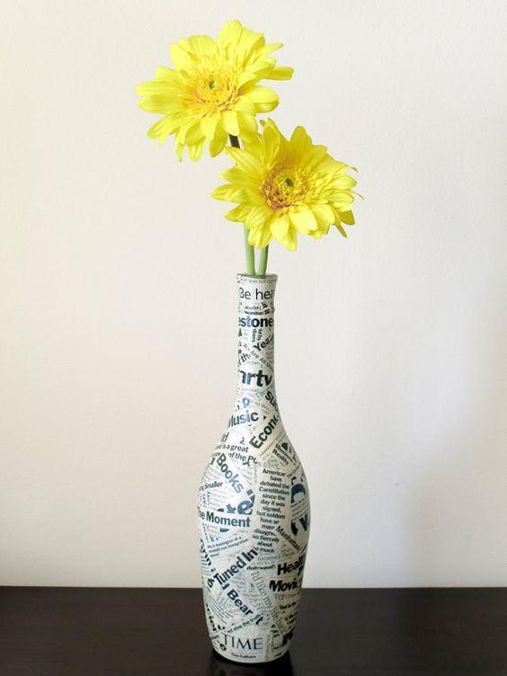 Vaso feito com garrafa de vinho e colagens de jornal. Uma opção simples e prática para se utilizar
