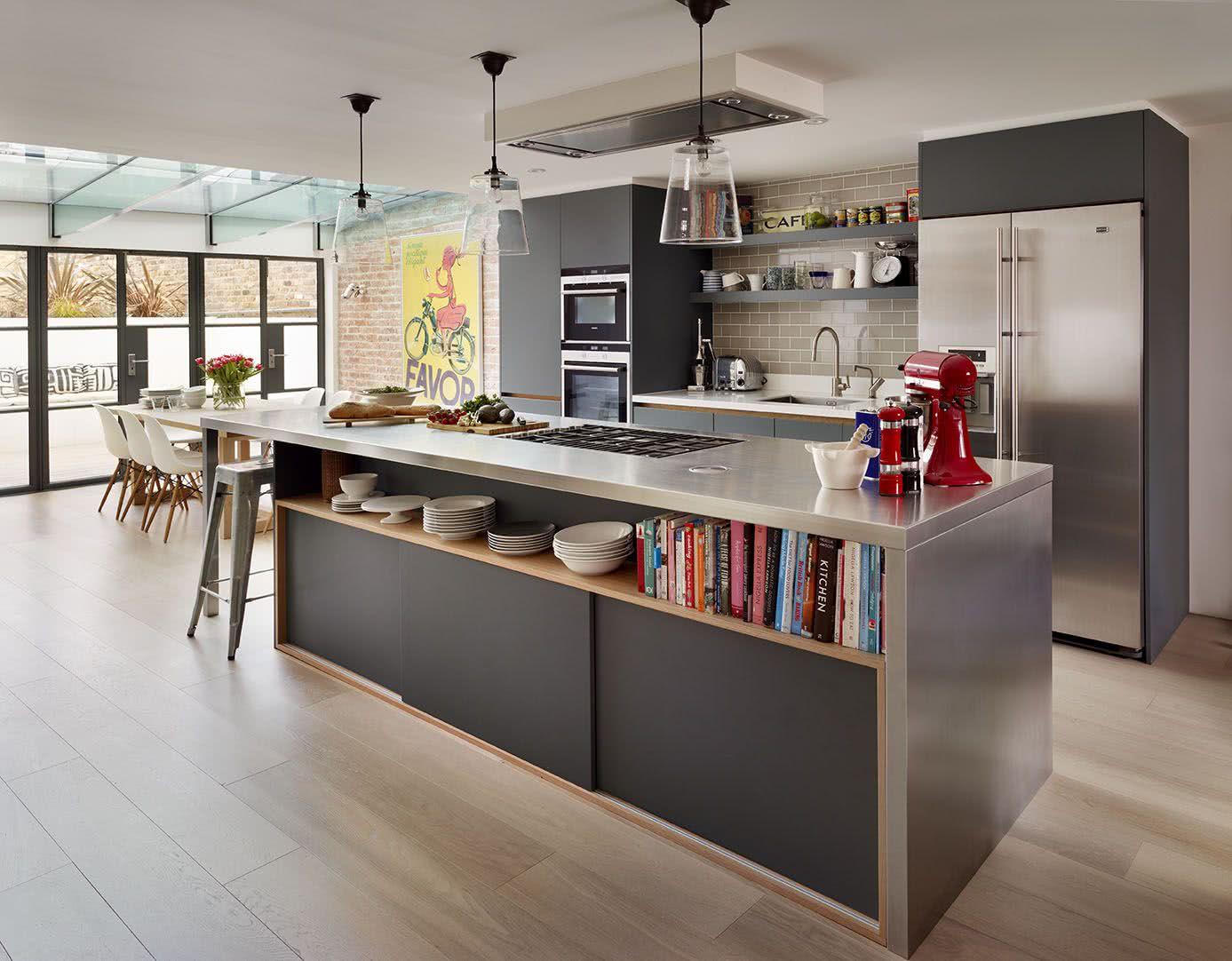 Cozinha com bancada em inox, parede com azulejo e piso em madeira