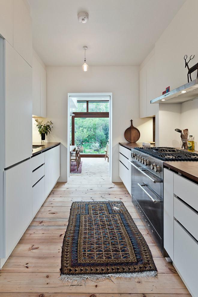 Ambiente da cozinha rústica predominantemente branco com bancada de madeira