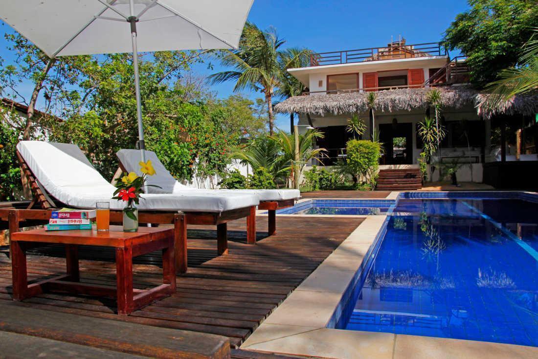 Para criar um espaço aconchegante ao lado da piscina, inserir poltronas e guarda sol garante sombra e um local confortável para relaxar
