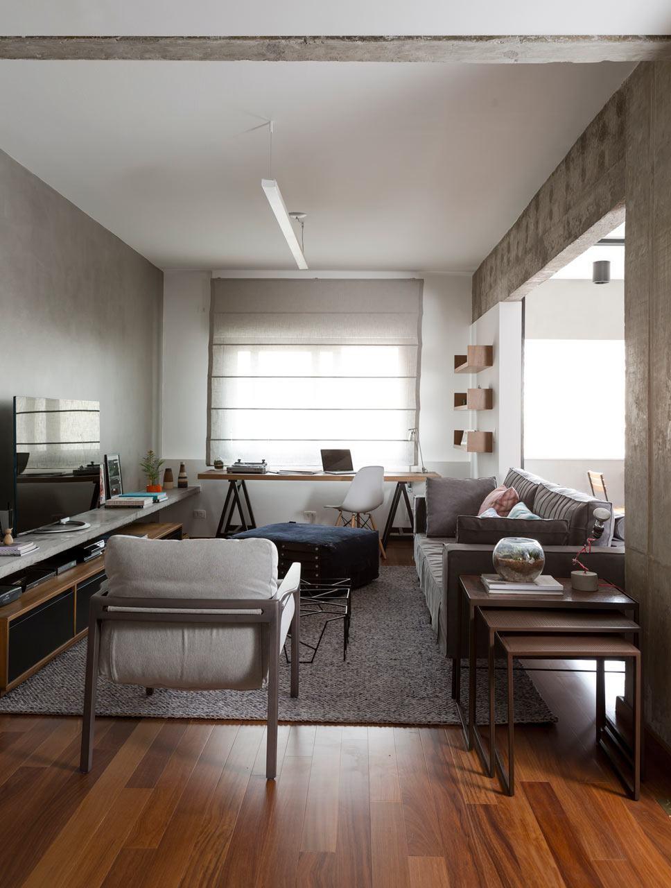 A combinação do piso em madeira e parede de concreto deixam a sala jovem e descolada