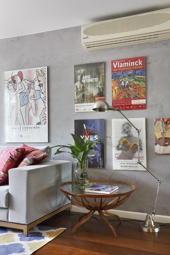 A parede de cimento queimado destaca ainda mais com quadros decorativos
