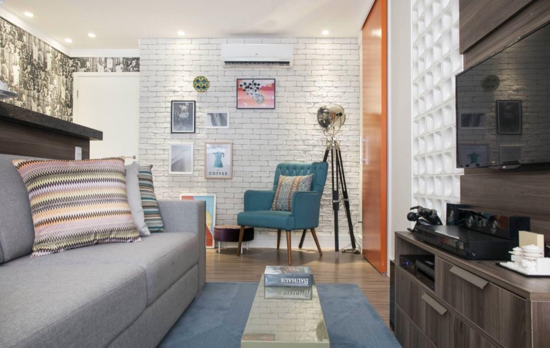 Salas decoradas: o toque jovial da sala se dá pelo tijolinho a vista, cobogós e almofadas coloridas