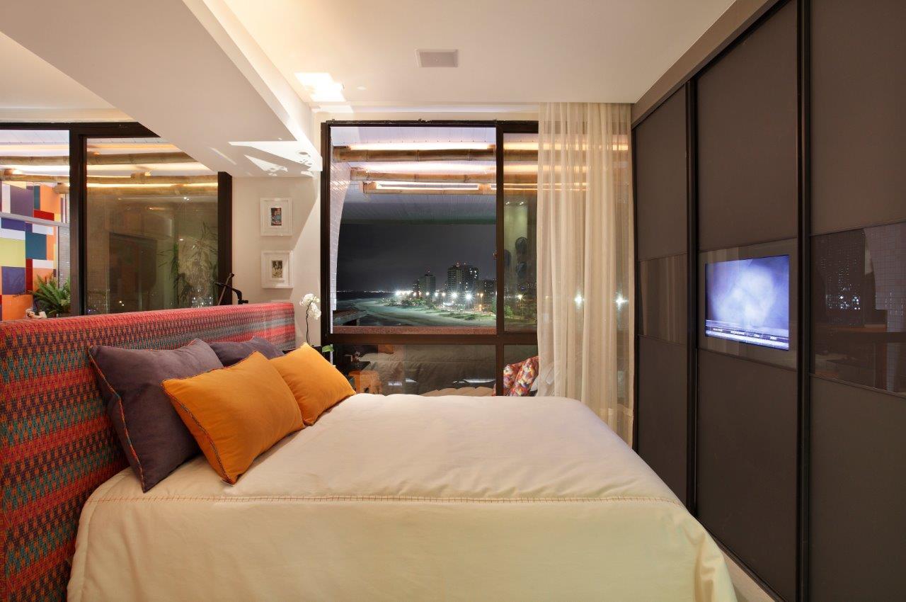 A TV embutida no espelho é moderna e otimiza o espaço para quartos pequenos.