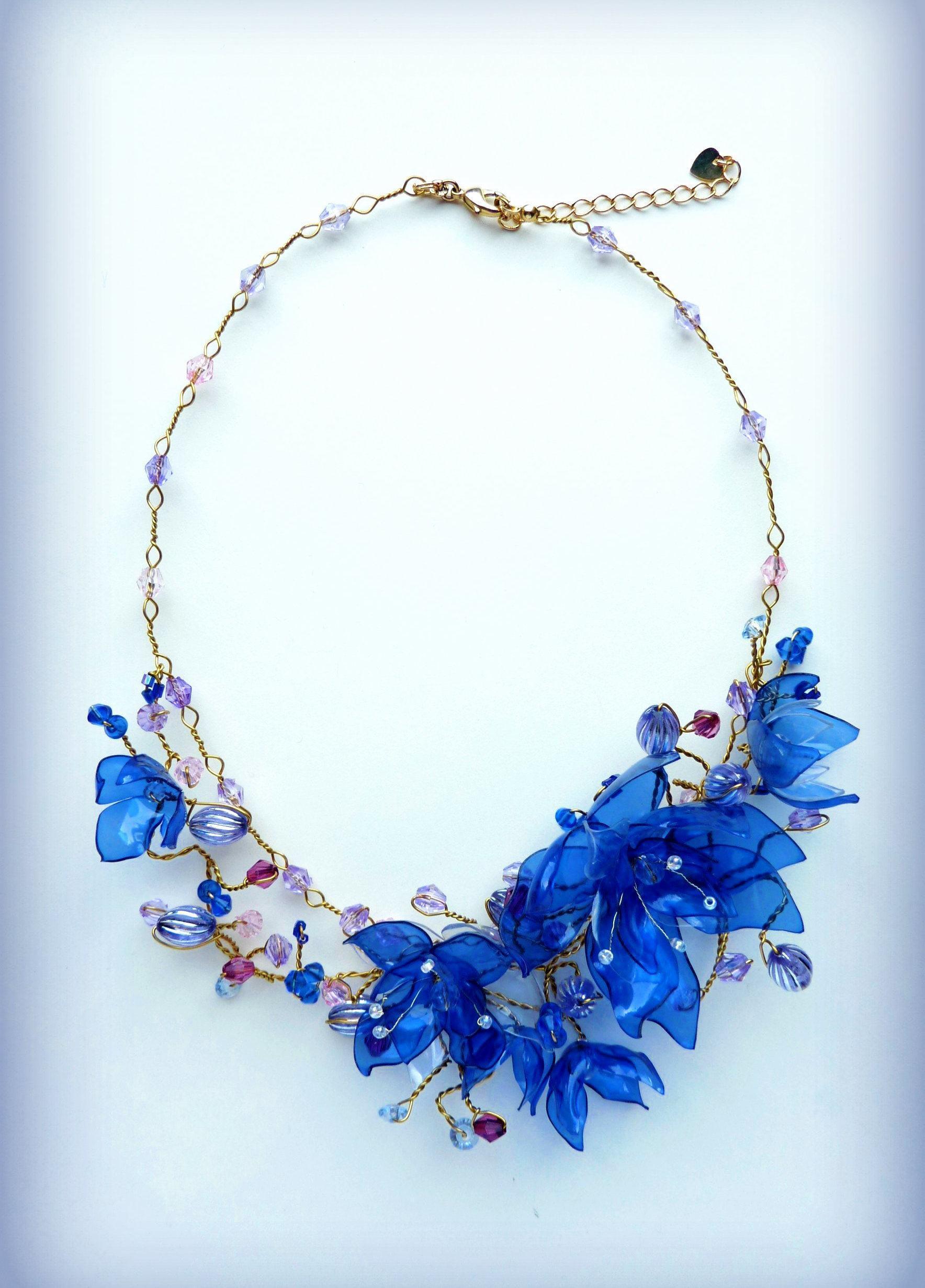 Colar dourado com flores azuis de plástico