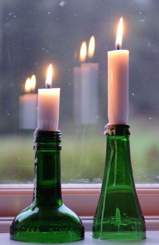 Porta velas feito com garrafa de vidro cortada.