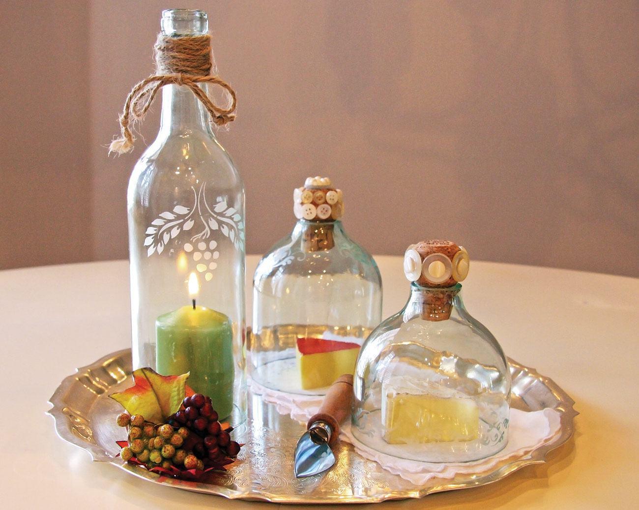 Garrafas de vidro cortadas que abrigam a vela e outros objetos.