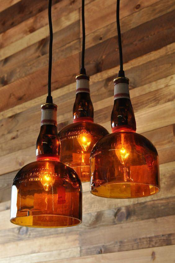 Luminária suspensa feita com garrafa de vidro alaranjada.