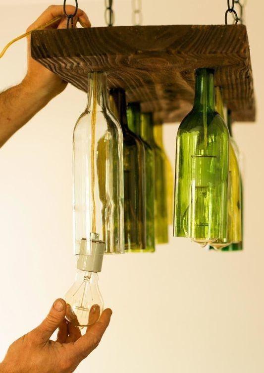 Luminária feita com madeira e garrafas de vidro suspensas.
