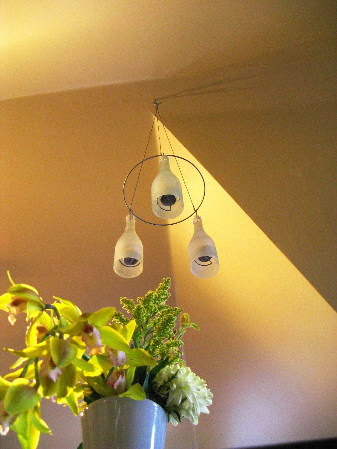 Luminária suspensa com garrafas de vidro.