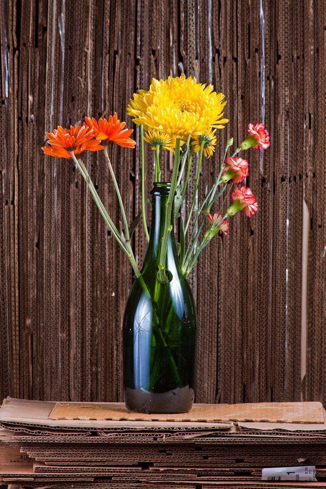 Vaso de garrafa de vidro com furos para abrigar flores.
