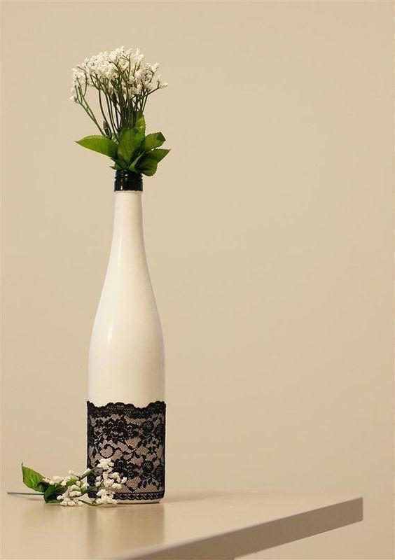 Garrafa de vidro pintada de branco como vaso de flores.