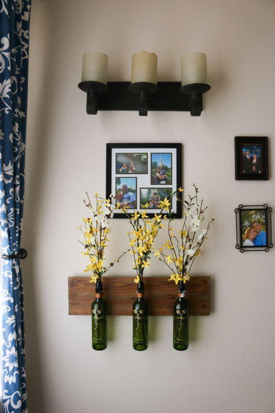 Vasos de garrafa de vidro para flores fixos a um suporte de madeira.