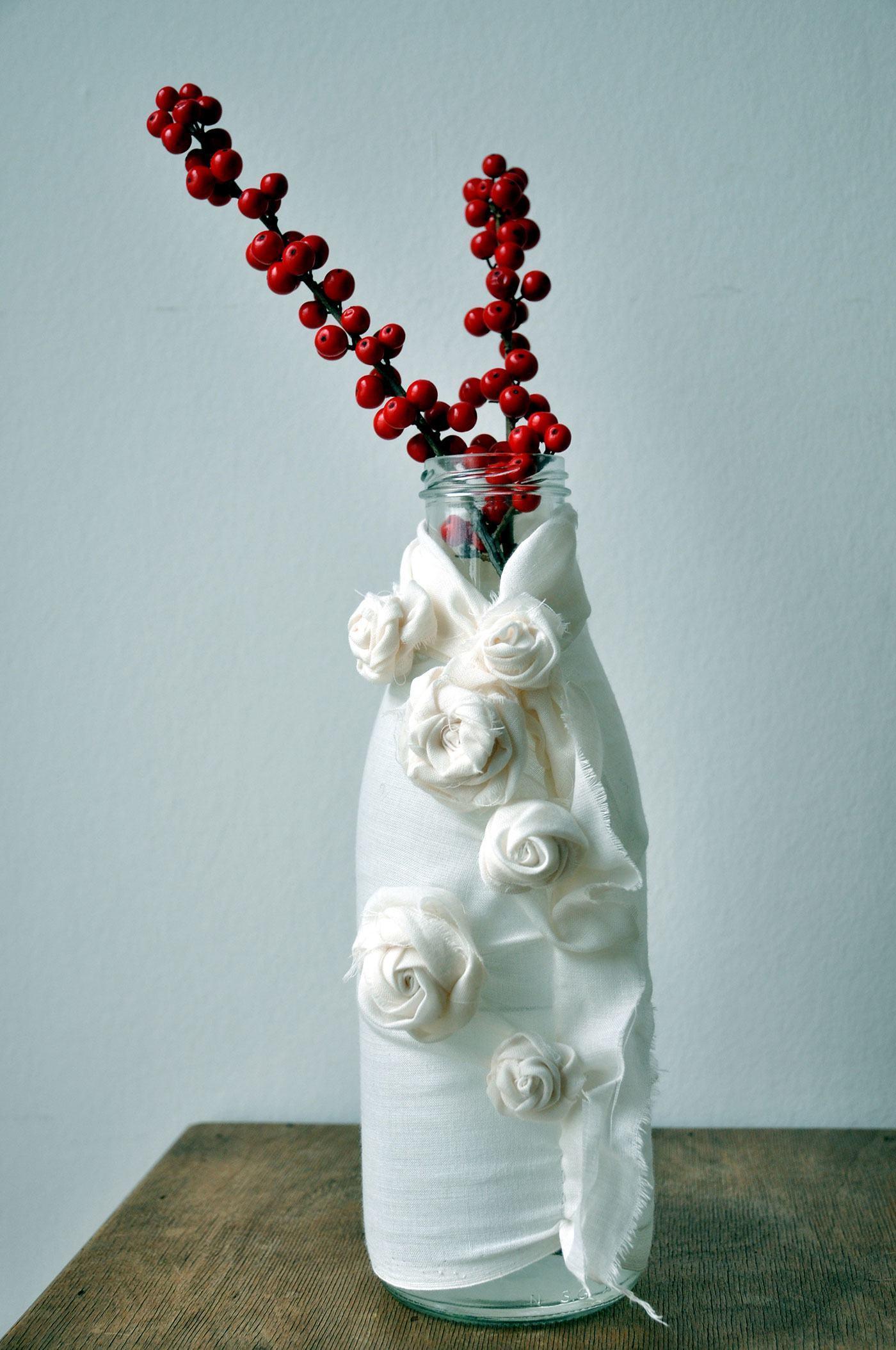 Garrafa de vidro como vaso revestida de tecido com flores.