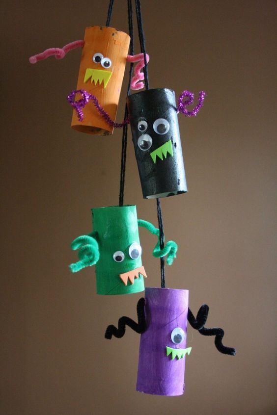 Pequenos monstrinhos coloridos feitos com rolo de papel e barbante.