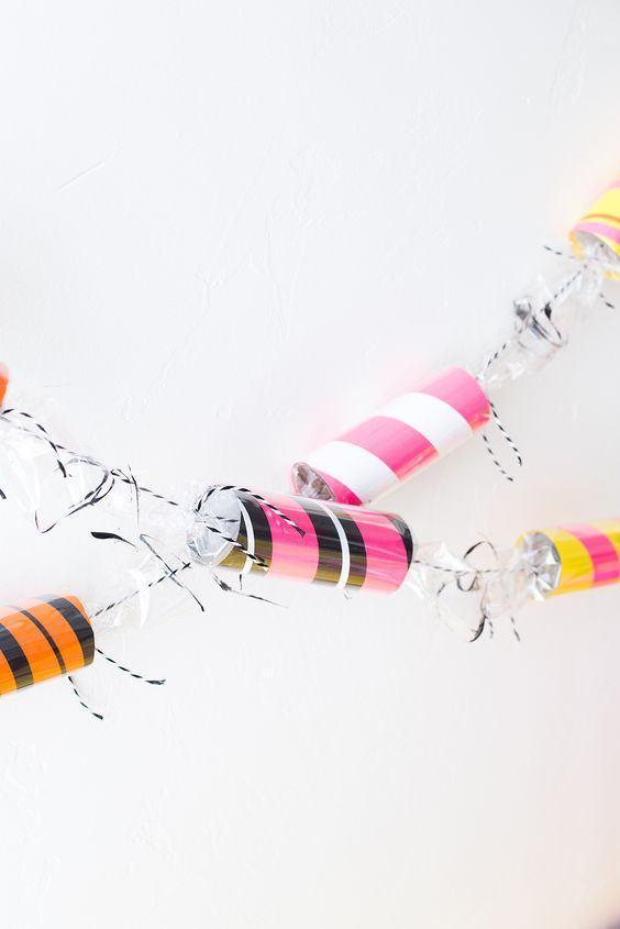 Enfeite para a festa com rolos revestidos de papéis listrados e coloridos.