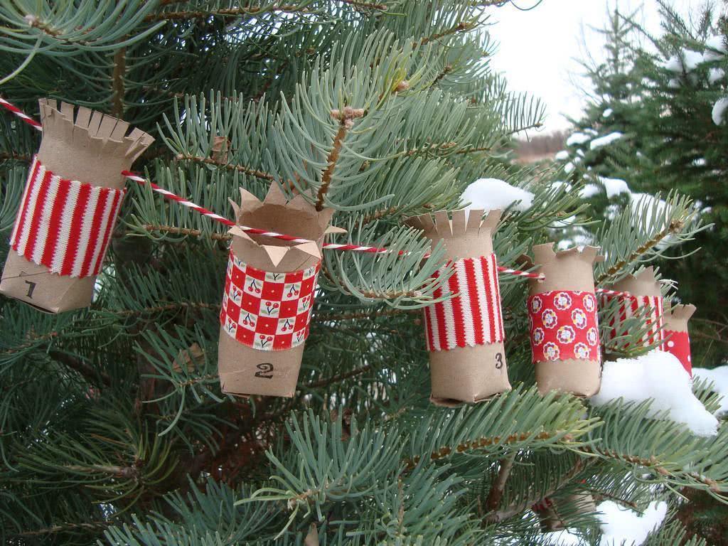 Rolos de papel recortados e unidos por barbante. Eles foram revestidos por tecidos com estampas natalinas.