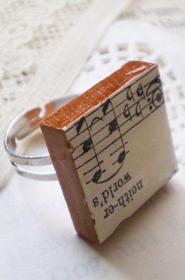 Anel com madeira e desenho de partitura.
