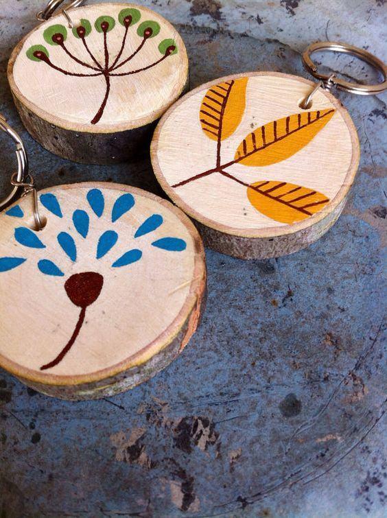 Chaveiros redondos de madeira com pinturas de árvores e folhas.