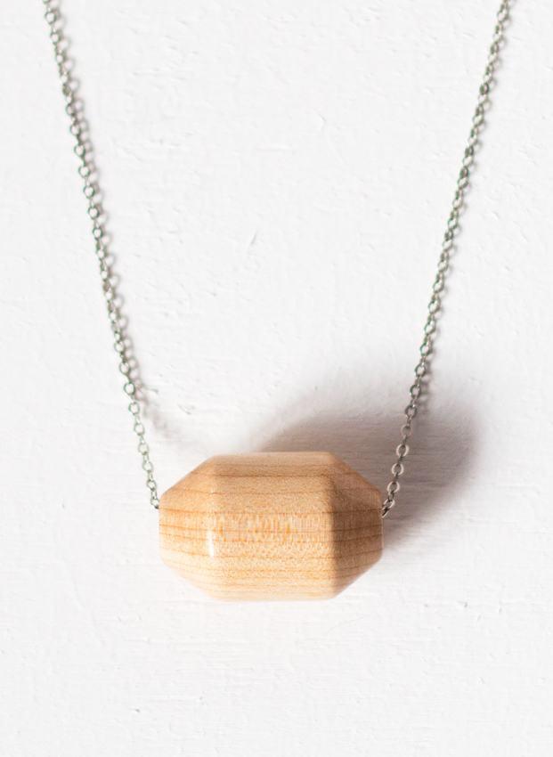 Colar de corrente metálica com pedaço geométrico de madeira.