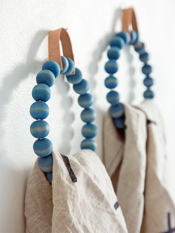 Suporte para sacolas com bolinhas de madeira pintadas.