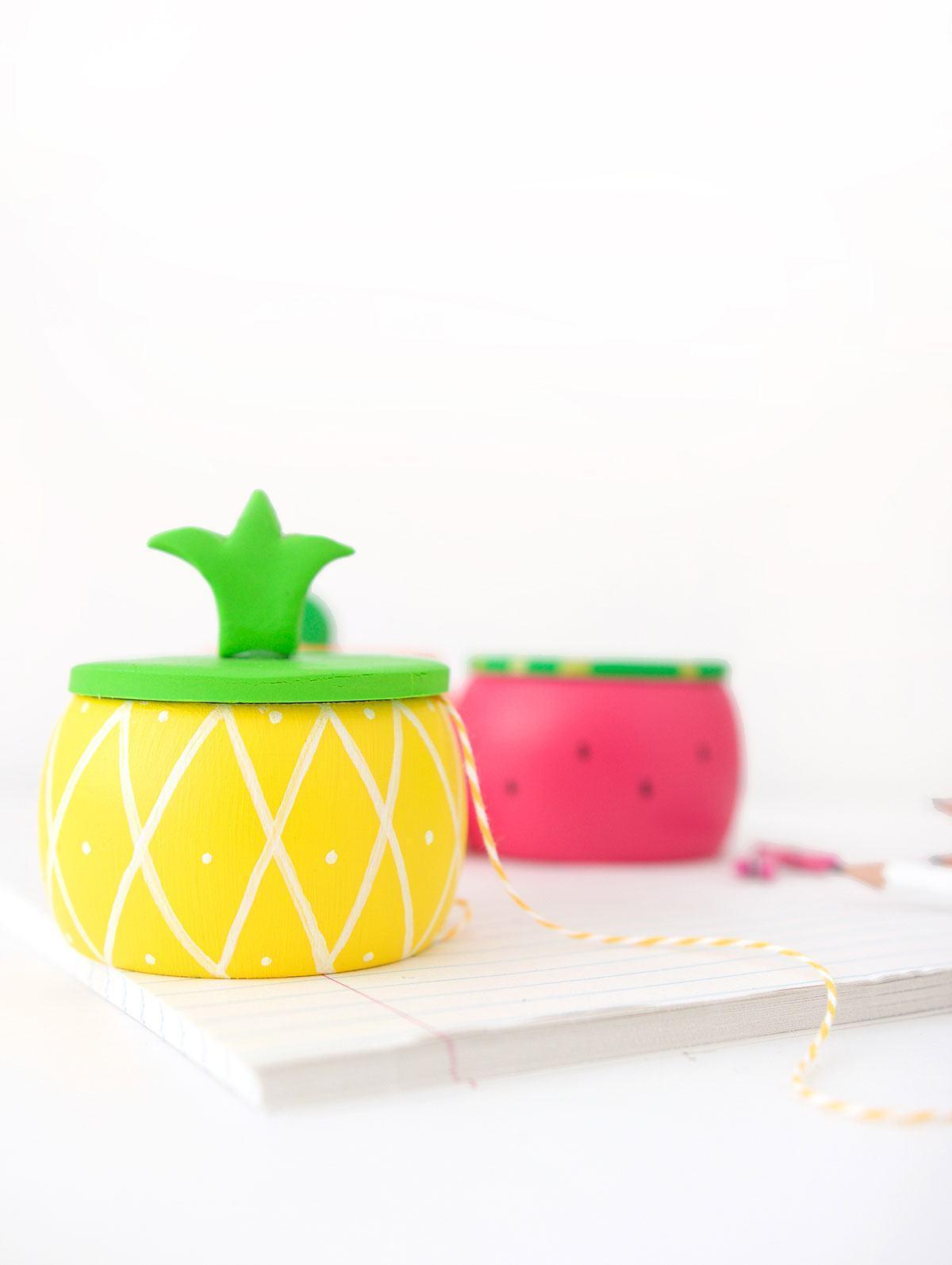Potes de madeira com formatos e cores de frutas.