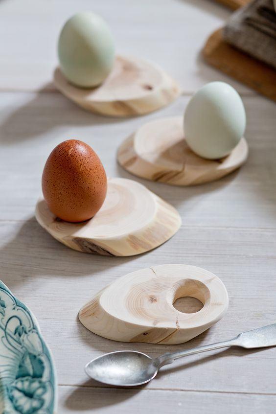 Pequenos suportes de madeira com furo para deixar os ovos dispostos na mesa.