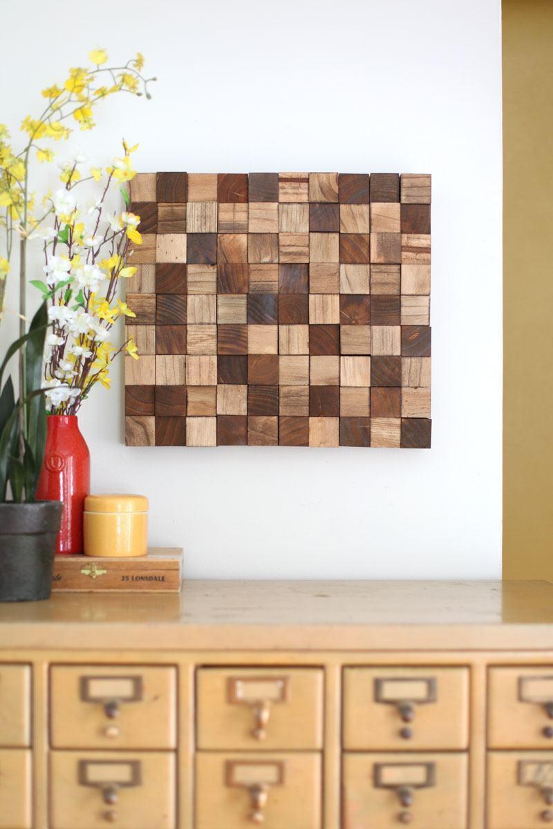 Objeto decorativo feito com cubos de madeira em diferentes tonalidades naturais.