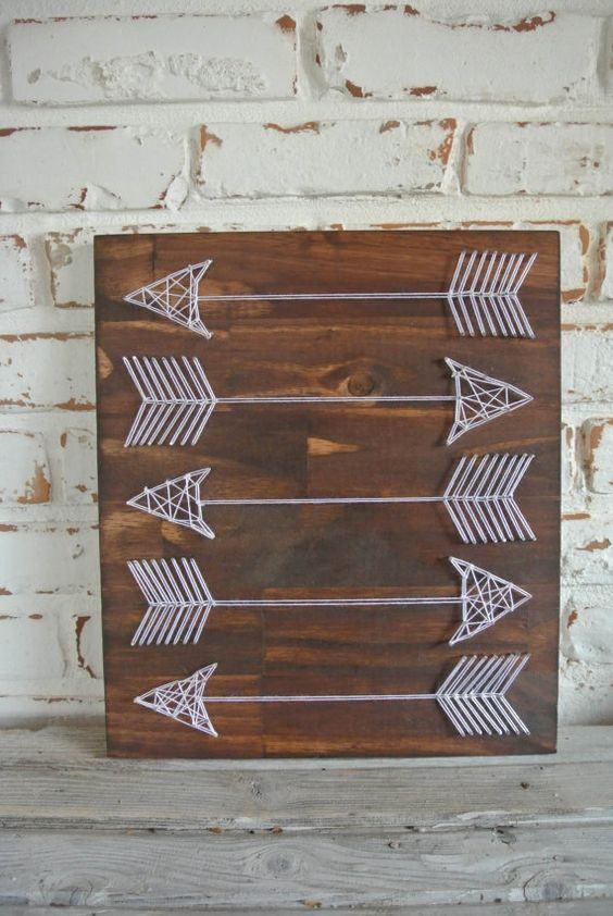 Quadro decorativo com flechas de barbante.